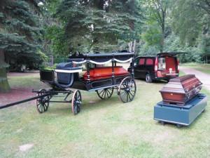 Bestattungswagen, -kutsche und Sarg auf dem Friedhof.