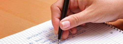 Hand mit Stift beim verfassen eines Briefes