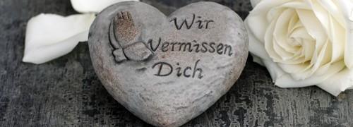 """Stein in herzform und der Inschrift """"Wir vermissen Dich""""."""