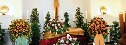 Trauerfeier: Traueraltar in einer Kirche mit Sarg und vielen Blumengestecken. Im Hintergrund ist ein großes, hölzernes Jesuskreuz zu sehen.