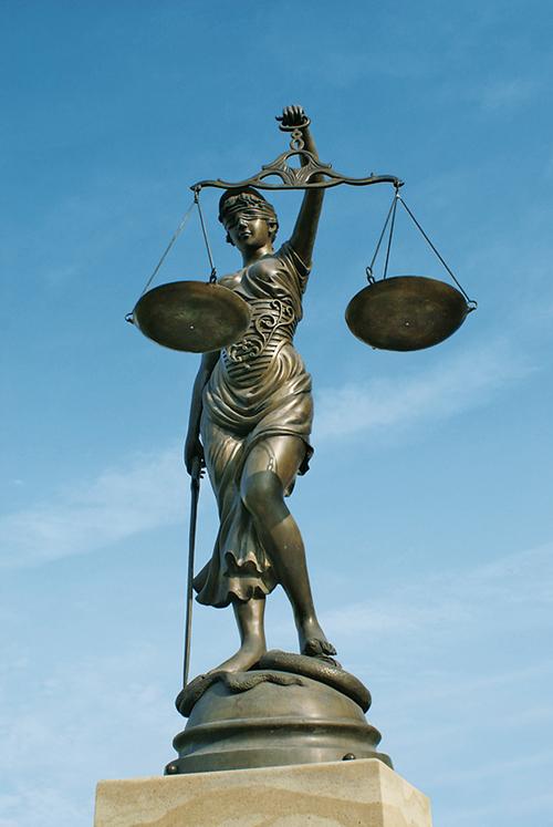 Justizia mit verbundenen Augen, Waage und Schwert vor blauem Himmel.