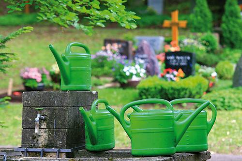 Grüne Gießkannen auf einem Friedhof.