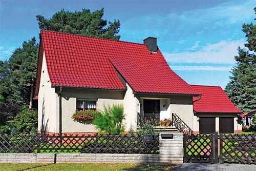 Ein Einfamilienhaus mit rotem Dach als Musterimmobilie.