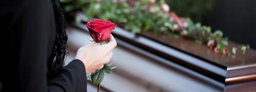 Eine schwarz gekleidete Frau hält eine rote Rose in der Hand und steht vor einem Sarg.