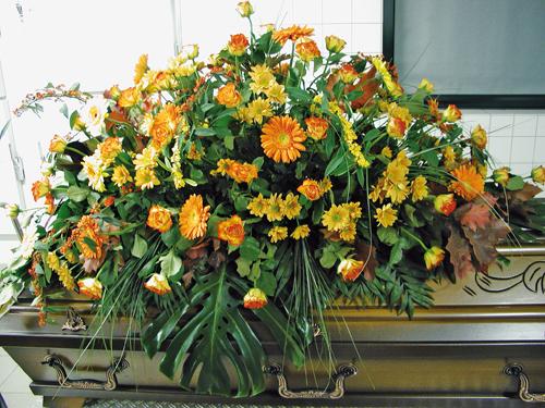 Blumengesteck auf einem Holzsarg.