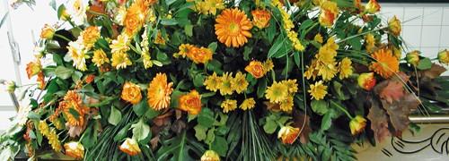 Blumenarrangement auf einem brauen Holzsarg.