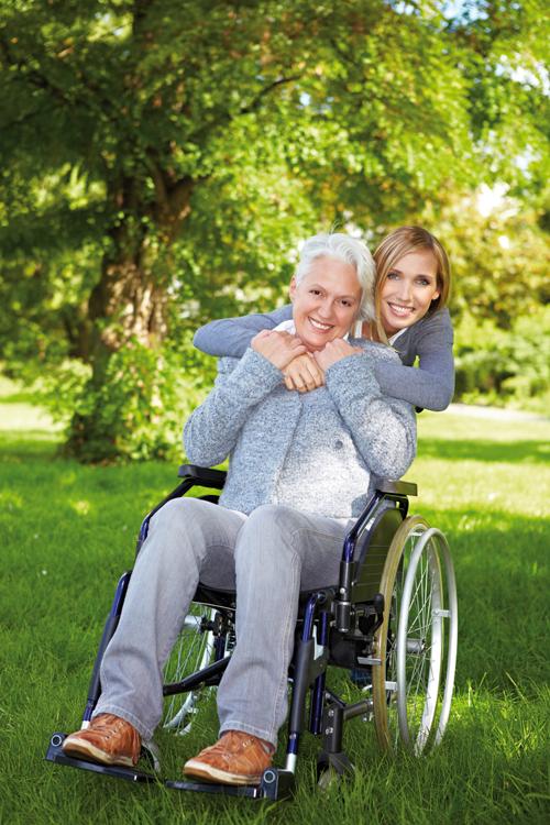 Mutter im Rollstuhl mit ihrer Tochter. Beide sind glücklich darüber, dass sie gemeinsam eine Vollmacht aufgesetzt haben.