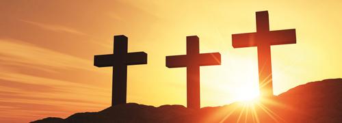 Drei Kreuze vor einem Sonnenuntergang.